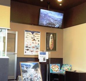 店の一隅にはスクリーンが津波の映像を流している。
